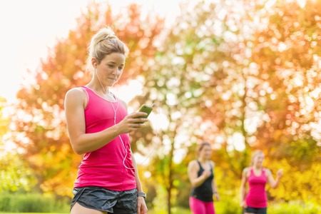 Portrait of an attractive woman using her smart phone to chose songs for a workout photo