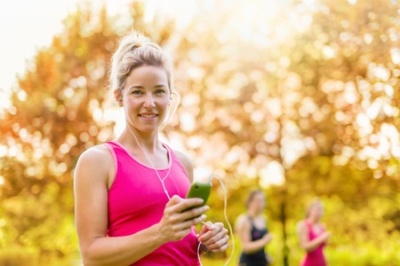 Portrait of a woman using her smart phone to chose songs for a workout photo