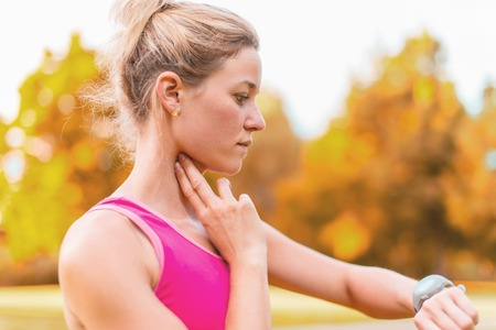 mesure: Portrait of an athlete using her watch to mesure her pulse while running in nature Stock Photo