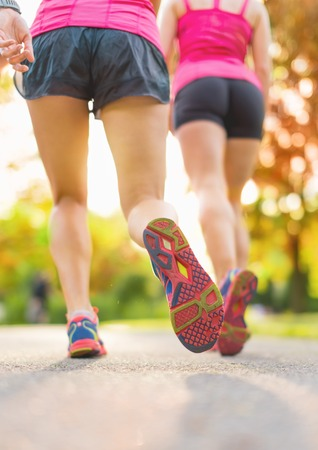 vertical close up of legs of a group of female runners outside in nature with lens flare