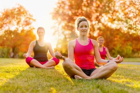 horizontale detail van een groep vrouwen doet yoga buitenshuis bij zonsondergang met lens flare. Ondiepe scherptediepte