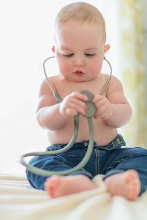 bebe enfermo: todler lindo escuchar a su coraz�n en un instrumento m�dico Foto de archivo