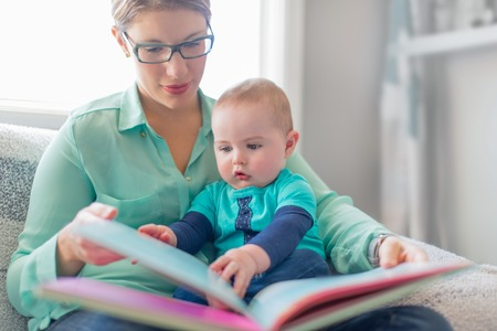 Adorable toddler flipping the pages of a picture book on his moms lap