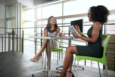 Couple of business female coworkers collaborating on a project in a bright glass office