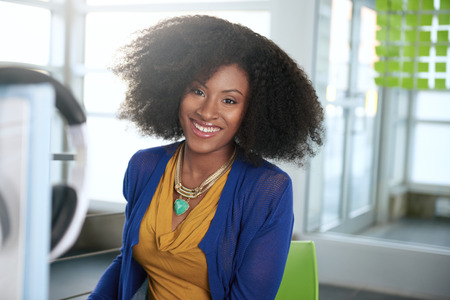 afro curly hair: Friendly african american casual business woman working at a desktop computer in a modern withe office