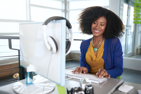 the programmer: Friendly african american casual business woman working at a desktop computer in a modern withe office