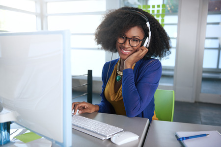 현대 가지 사무실에서 데스크톱 컴퓨터에서 작업 친화적 인 아프리카 계 미국인 캐주얼 사업 여자