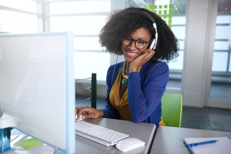 ležérní: Friendly afro-americké ležérní obchodní žena pracující na stolním počítači v moderní kanceláře prutů