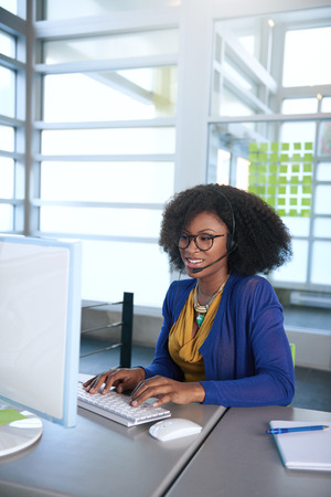 African american bienvenus centre d'appels occasionnels emplyee travailler à un ordinateur de bureau dans un bureau moderne withe
