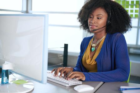 mujeres africanas: Amistoso afroamericano emplyee call center ocasional que trabaja en una computadora de escritorio en una oficina moderna withe