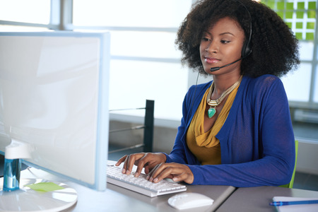 customer: Friendly african american casual call center emplyee working at a desktop computer in a modern withe office