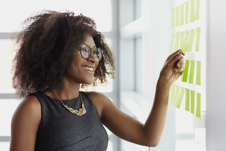 working woman: Friendly african american executive business woman brainstorming using green adhesive notes in a modern white office