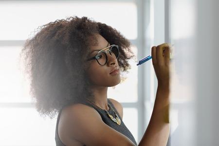 mujeres trabajando: Amistoso africano mujer de negocios ejecutivo americano de intercambio de ideas usando verdes notas adhesivas en una oficina moderna blanca