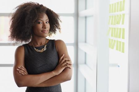 cheerful woman: Amistoso africano mujer de negocios ejecutivo americano de intercambio de ideas usando verdes notas adhesivas en una oficina moderna blanca