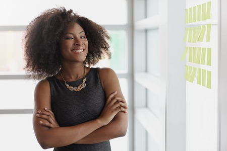 Friendly african american executive business woman brainstorming using green adhesive notes in a modern white office