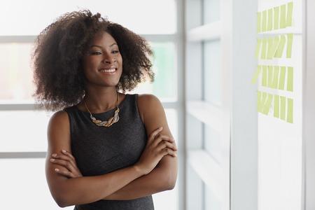 Vriendelijke Afro-Amerikaanse vrouw uitvoerende bedrijf brainstormen met behulp van groene zelfklevende notities in een moderne witte kantoor