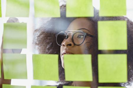 mujer pensativa: Amistoso africano mujer de negocios ejecutivo americano de intercambio de ideas usando notas adhesivas en una oficina moderna blanca