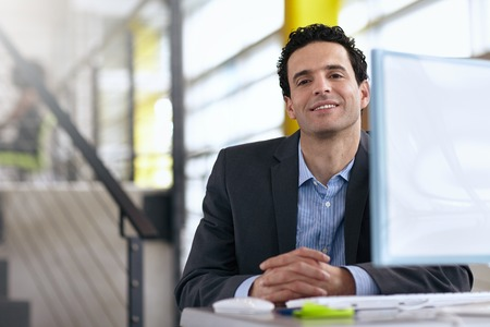 office space: Friendly man sitting at a desk in a modern bright office