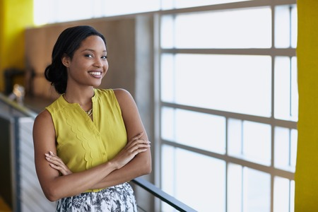 woman looking: Friendly african american woman standing with arms crossed in a modern bright office