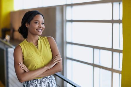 Vriendelijke Afro-Amerikaanse vrouw stond met de armen gekruist in een moderne lichte kantoor