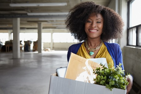 cardboard only: Friendly african american woman moving to her new starup office in an industrial office