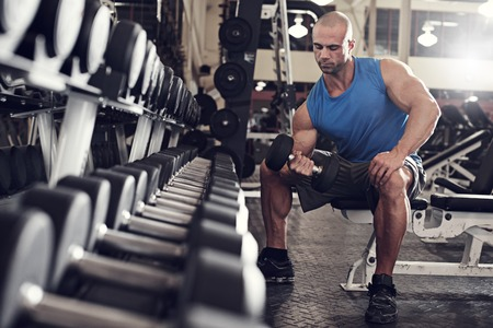 active and muscular man keeping his arms strong muscular and fit by using free weights- filtered image Archivio Fotografico