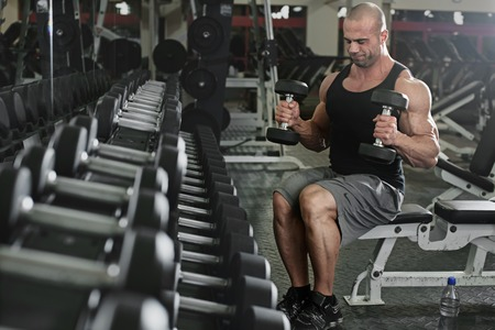 body building: active and muscular man keeping his arms strong muscular and fit by using free weights- filtered image Stock Photo