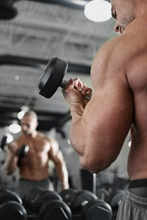 free weights: active and muscular man keeping his arms strong muscular and fit by using free weights in front of the mirror - filtered image