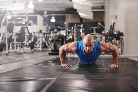 keeping fit: active and muscular man keeping fit by doing pushups on a floor mat - filtered image