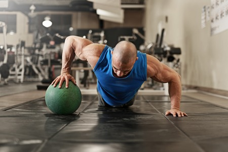body building: active and muscular man keeping fit by doing pushups using a medecine ball - filtered image Stock Photo