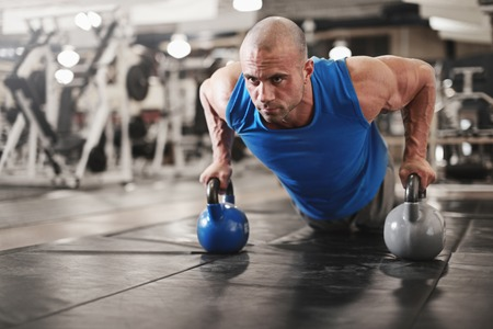 gym ball: active and muscular man keeping fit by doing pushups using kettle bells- filtered image
