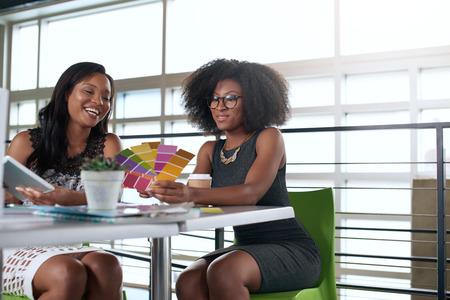 afroamericanas: Un par de compañeros de trabajo de negocios colaborar en un proyecto en una oficina de cristal brillante