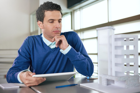 architect office: Serious architect going over digital plans on a touch screen tablet in a brightly lit office Stock Photo