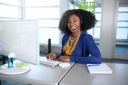 Vriendelijke Afro-Amerikaanse informele call center emplyee werken op een desktop computer in een modern kantoor knutselen