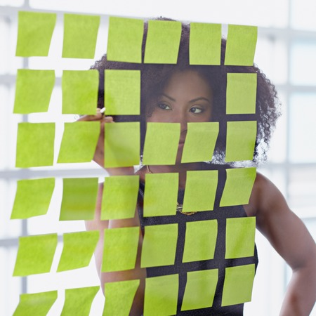 Friendly african american executive business woman brainstorming using adhesive notes in a modern white office
