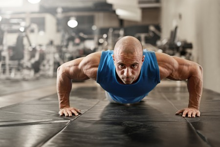 exercise man: active and muscular man keeping fit by doing pushups on a floor mat - filtered image