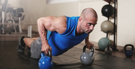 keeping fit: active and muscular man keeping fit by doing pushups using kettle bells- filtered image