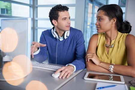Paar van het bedrijfsleven collega's samen te werken aan een project in een heldere glazen kantoor Stockfoto