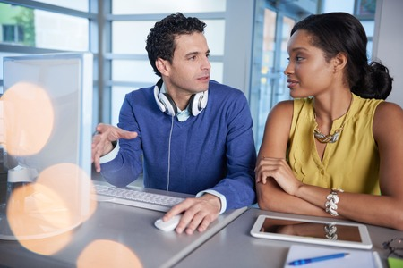 empleado de oficina: Un par de compañeros de trabajo de negocios colaborar en un proyecto en una oficina de cristal brillante