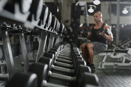free weights: active and muscular man keeping his arms strong muscular and fit by using free weights- filtered image Stock Photo