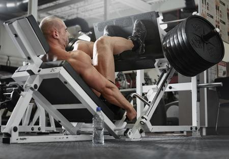 uomo attivo e muscoloso tenendo le gambe forte e in forma utilizzando attrezzature palestra machinnes - immagine filtrata Archivio Fotografico
