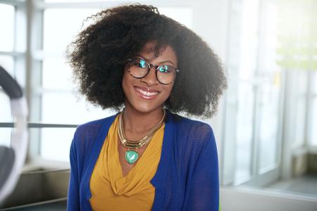Vriendelijke Afro-Amerikaanse casual zakenvrouw werken op een desktop computer in een modern kantoor knutselen