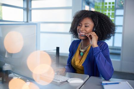 servicio al cliente: Amistoso afroamericano emplyee call center ocasional que trabaja en una computadora de escritorio en una oficina moderna withe