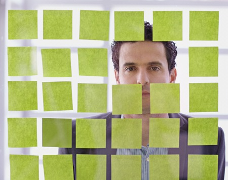 Serious executive business man brainstorming using green adhesive notes in a modern white office