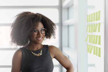 african business: Friendly african american executive business woman brainstorming using green adhesive notes in a modern white office