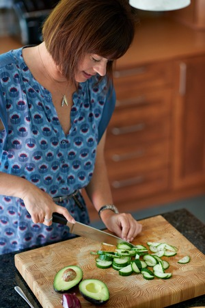 people only: lady in her forties preparring avocado and cucumber for a rustic salad Stock Photo