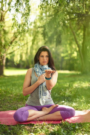 mat like: Portrait of beautiful mixed race caucasian, african, middle eastern girl meditating and doing yoga at sunset on the grass in a park or forrest Stock Photo