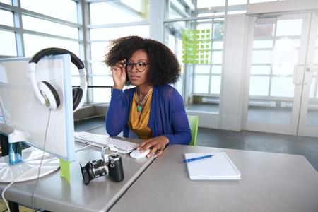 Amistoso afroamericano mujer de negocios informales que trabajan en una computadora de escritorio en una oficina moderna withe