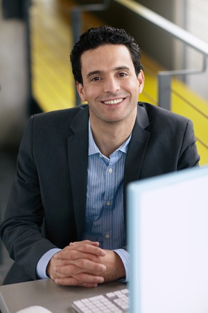 현대 밝은 사무실에서 책상에 앉아 친절한 남자