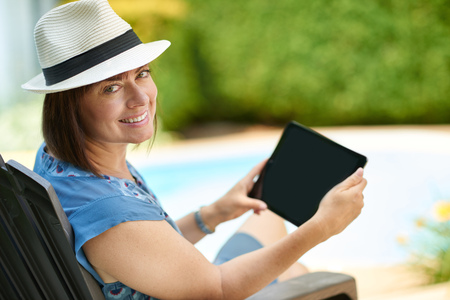 forties: Modern lady in her forties reading emails on a wireless tablet in in her pool side backyard